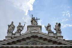 Standbeelden van Christus en sommige heiligen op de bovenkant van de voorzijde van Heilige Peter Basilica stock foto's