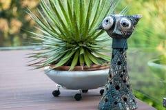 Standig de las ilustraciones del gato delante de un cactus suculento en una terraza fotos de archivo libres de regalías