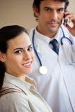 Женщина усмехаясь пока доктор Standing В Предпосылка Стоковые Фотографии RF