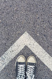 Standing above arrow shaped sign on the road, top view. Man standing above arrow shaped line sign on urban pavement, top view of young male feet wearing sneakers Stock Photography