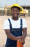 Standing african construction worker with pipe Royalty Free Stock Photos