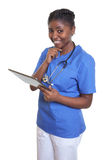 Standing african nurse working with tablet computer Royalty Free Stock Photo