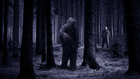 Standing alone against zombies. A man in a forest surrounded by zombies stock images