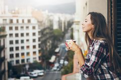 Side view of cheerful young girl looking happy and smiling and drinking cup of appetizing coffee. While standing at apartment balcony terrace with an urban view Stock Photos