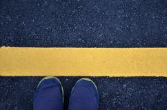 Standing on asphalt ground with yellow line. On the road Stock Photo