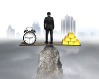 Standing and balancing with clock and bullion Stock Images
