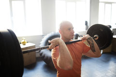Standing Barbell Shoulder Press. Concentrated bodybuilder doing shoulder press exercise with barbell in gym illuminated with bright sunlight stock image