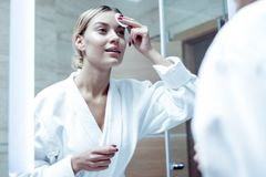 Appealing beautiful woman wearing white bathrobe standing in bathrobe. Standing in bathrobe. Appealing beautiful woman wearing white bathrobe standing in royalty free stock photography