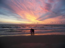 Standing on the beach. Three children standing on the beach at sunset stock image