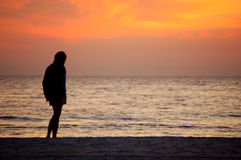 Standing On The Beach. Woman standing alone on the beach at sunset Stock Photo