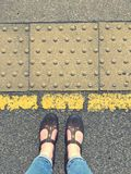 Standing behind the yellow line with sandals. Standing behind the yellow line on a station platform, feet with sandals on stock photography