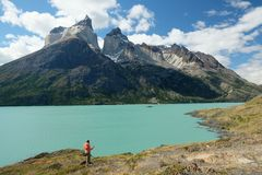 Standing below Los Cuernos, Torres del Paine, Patagonia, Chile. Standing below jagged peaks of Los Cuernos in Patagonia.  Orange pink jacket framed in front of stock photography