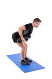 Standing Bent Over Dumbbells Row workout. Young man shows finishing position of Standing Bent Over Dumbbells Row workout, isolated on white royalty free stock images