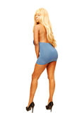 Standing blond woman in blue dress 85. An friendly blond girl in an very short blue dress standing in an studio with Royalty Free Stock Photos