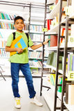 Standing boy with books in school library. Putting book on the shelf Stock Photo
