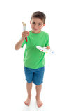 Standing boy holding paints and brushes. A young boy stands holding or showing paints and paint brushes. White background stock photography