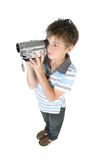 Standing boy using a digital video camera Royalty Free Stock Image