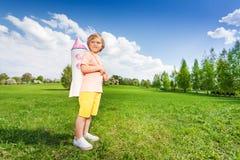 Standing boy wears paper rocket toy on shoulders Stock Image
