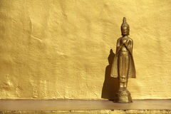 Standing Buddha Image And Golden Wall. A golden Buddha image in front of a golden wall casts a contrasting shadow on the background stock images