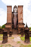 Standing Buddha statue behind pillars vertical Royalty Free Stock Photos