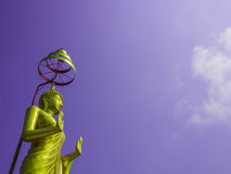 Standing Buddha Statue. Standing golden buddha statue and blue sky Stock Photo