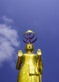 Standing Buddha Statue. Standing golden buddha statue and blue sky Royalty Free Stock Images