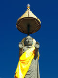 Standing Buddha statue soars into blue sky Stock Photos