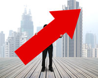 Standing businessman holding red arrow sign Stock Images