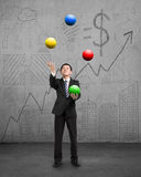 Standing businessman playing colorful balls. On concrete floor with doodles wall Royalty Free Stock Photos