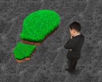 Standing businessman pondering over green grass of light bulb stock image