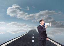 Standing businessman shouting through a megaphone Stock Images