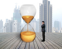 Standing businessman thinking with hourglass Royalty Free Stock Image