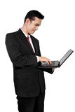 Standing businessman using laptop, isolated on white Royalty Free Stock Image