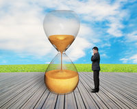 Standing businessman watching the hourglass. With nature sky and wooden floor royalty free stock image