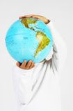 Standing child boy holding a globe in hands in front of his head Royalty Free Stock Photos