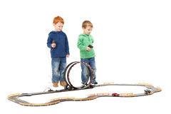 Standing children playing kids racing toy car game. Standing children playing kids racing toy electric slot car game. On white stock photography