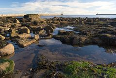 Standing clear water between stones made by outflow, blue water reflection of the sky and Tynemouth pier behind, UK. Standing clear water between stones made by royalty free stock images