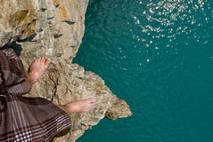 Standing on a Cliff. A man stands on a cliff, with a long drop to the water below Royalty Free Stock Photography