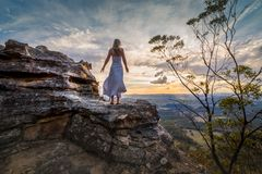 Standing on a cliff edge with dress blowing in the wind she dreams royalty free stock photos
