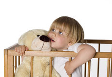 Standing in cot hugging Teddybear little girl Stock Photography