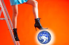 Standing On The Earth. Woman standing on a stepladder with one foot.  Her other leg is bent in the air above a glowing replica of the earth.  Woman shot from the Royalty Free Stock Photo