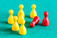 Standing and fallen red pawn near yellow pawns stock photo