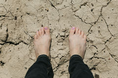 Standing feet on cracked ground Royalty Free Stock Images
