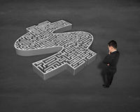 Standing in front of 3d money shape maze. On concrete ground Stock Photo
