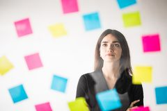 Standing in front of glass wall young business woman with post it stickers. office decision. stock images