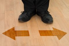 Standing in front of left or right arrows on floor Stock Photos