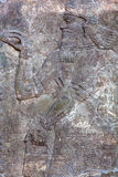 Standing Genie - ancient relief slab from a wall from the palace Stock Image