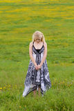 Standing girl on meadow in spring,. Standing girl on green meadow in spring, looking down stock image