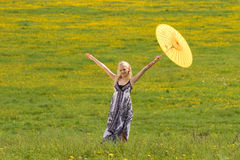 Standing girl with parasol on. Standing girl with yellow parasol on meadow, arms raised stock image
