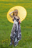 Standing girl with parasol on. Standing girl with yellow parasol on meadow in spring, arm raised royalty free stock photos